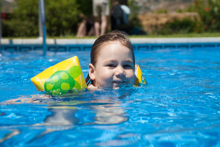 three years old blonde child with yellow floater sleeves in arms looking face swimming in blue water of swimming pool