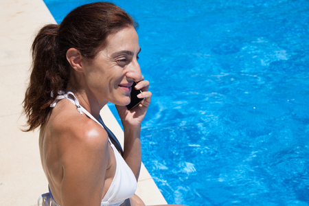 curb: brunette woman wearing white bikini sitting on the curb of pool talking on mobile phone with blue water behind Stock Photo