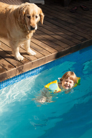 floater: big Golden Retriever dog looking at three years old happy blonde child laughing with yellow floater sleeves in arms in blue water of swimming pool