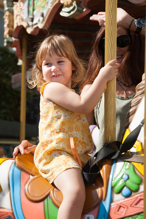 vivo: portrait of three years old blonde pretty girl with yellow dress sitting on a colorful horses  in a carousel, next to brunette woman mother smiling