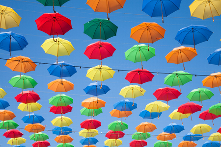 colourful sky: sky full of blue, red, green, orange and yellow color umbrellas in row covering a public street in Torremolinos city, Andalusia, Spain Europe
