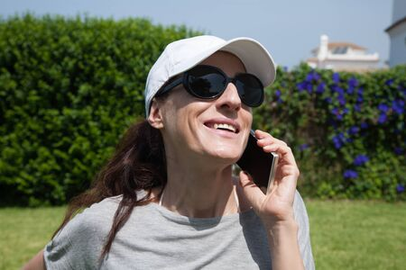 portrait of brunette woman with white cap, black sunglasses and grey shirt smiling and  listening to mobile phone smartphone with green plants garden background Stock Photo