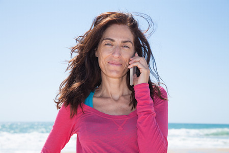 portrait of brunette woman looking with pink sweater smiling and listening to mobile phone smartphone at beach with sea and blue sky behind