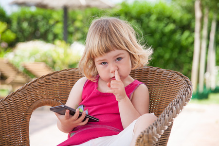 blonde caucasian girl two years old, summer red and white dressed, sitting on wicker chair with smartphone or mobile phone in her hand, finger in nose and looking