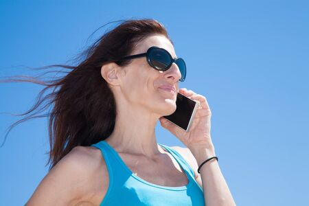 profile portrait of brunette woman with black sunglasses and blue cyan shirt smiling and listening to mobile phone smartphone at beach Stock Photo