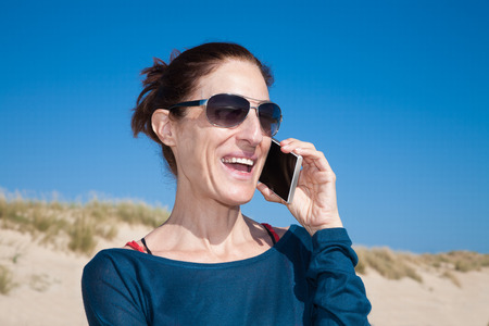 portrait of brunette woman with blue sweater and sunglasses looking side smiling and talking on mobile phone smartphone at beach with dune and sky behind Stock Photo