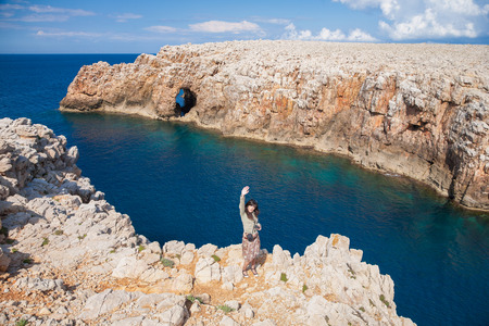 menorca: brunette woman with jacket greeting with hand up standing on cliff above ocean and rock cape in coast of Menorca, Balearic Islands, Spain, Europe Stock Photo