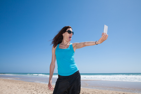 sticking out tongue: portrait of brunette woman with black sunglasses and blue cyan shirt teasing sticking out tongue making selfie with mobile phone smartphone at beach with sea behind
