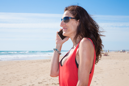 portrait of brunette woman looking side with sunglasses and red shirt smiling and talking on mobile phone smartphone at beach with sea and blue sky behind Stock Photo