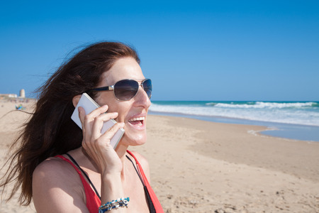 portrait of brunette woman looking side with sunglasses smiling and talking on mobile phone smartphone at beach with sea and blue sky behind Stock Photo