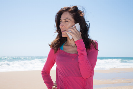 portrait of brunette woman looking side with pink sweater smiling and listening to mobile phone smartphone at beach with sea and blue sky behind Stock Photo