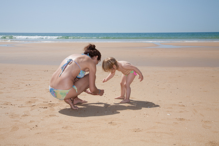 summer family of two years old blonde baby with green swimsuit and woman mother or babysitter blue bikini looking for, picking and collecting sea shells at golden sand beach seaside
