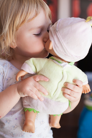 kissing mouth: lovely and tender scene of blonde caucasian cute baby two years old kissing on the mouth a doll in hands indoor Stock Photo
