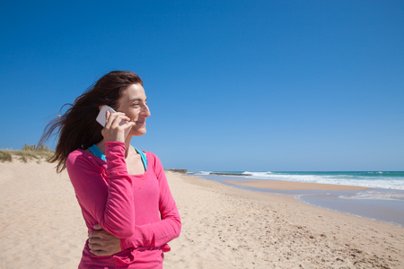 portrait of brunette woman looking side with pink sweater smiling and talking on mobile phone smartphone at beach with sea and blue sky behind Stock Photo
