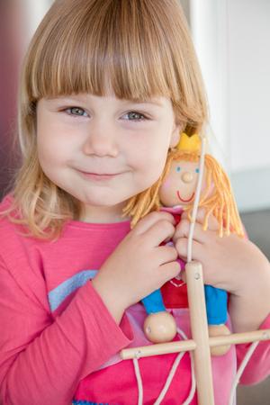 marioneta de madera: Retrato de la cara tres años del niño con la explosión rubia y camisa de color rosa, la celebración de la marioneta de madera en las manos mirando sonriendo