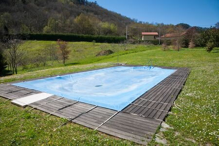 swimming pool with wooden curb closed and covered with blue tarp in Spring green meadow rounded by mountains in Nature in Asturias Spain Europe Stock Photo