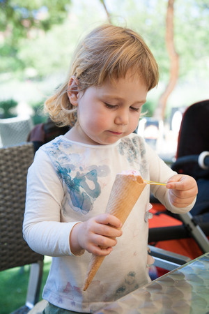 portrait of two years old blonde cute child with white shirt  eating strawberry ice cream cone with spoon, at urban park