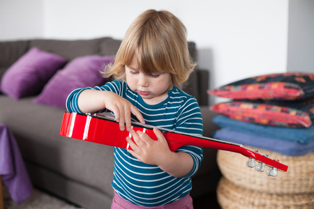 spanish home: blonde two years old child with striped blue and white sweater inside home playing with hand red spanish little guitar Stock Photo
