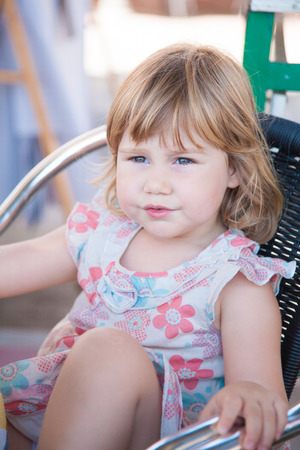 portrait of three years old blonde pretty girl with dress sitting on a chair and looking side