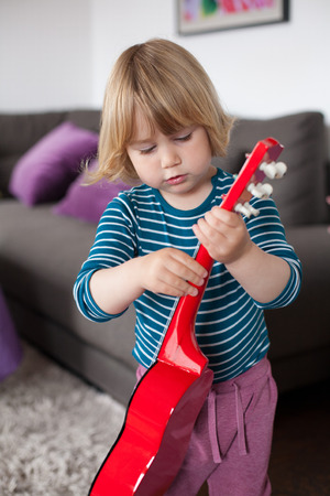 spanish home: blonde two years old child with striped blue and white sweater playing red spanish little guitar inside home