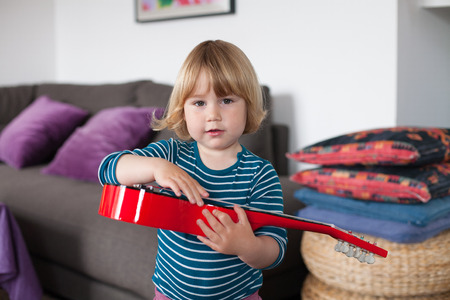 spanish home: blonde two years old child with striped blue and white sweater inside home playing with hand red spanish little guitar and looking Stock Photo