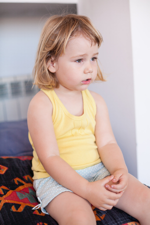 astonish: side portrait of blonde two years old child with yellow shirt sitting and watching open mouth