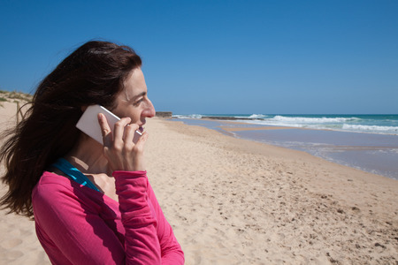 profile portrait of brunette woman looking side with pink sweater smiling and talking on mobile phone smartphone at beach with sea and blue sky behind