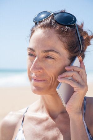 portrait of brunette woman with black sunglasses on head and white and grey bikini  smiling and listening to mobile phone smartphone at beach