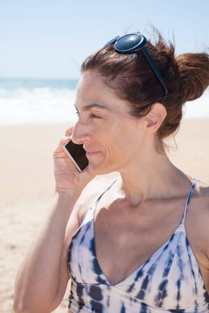 profile portrait of brunette woman with black sunglasses on head and white and grey bikini  smiling and listening to mobile phone smartphone at beach looking side