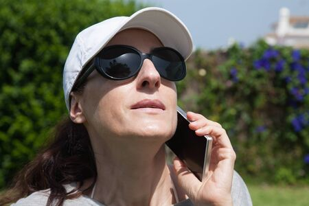 portrait of brunette woman with white cap, black sunglasses and grey shirt listen to mobile phone smartphone with green plants garden background Stock Photo