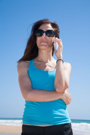 portrait of brunette woman with black sunglasses and blue cyan shirt smiling and listening to mobile phone smartphone at beach Stock Photo