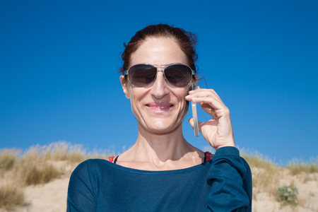 portrait of brunette woman with blue sweater and sunglasses looking smiling and talking on mobile phone smartphone at beach with dune and blue sky behind