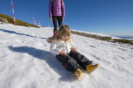 three years old blonde child with black trousers and white coat sitting on snow next to woman in summit of Navacerrada mountain, in Madrid Spain