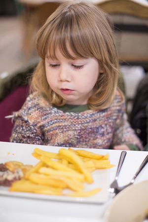 Three years old blonde cute caucasian child with knitted sweater eating french fries and meat with white dish at restaurant