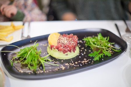 black plate tray with red tuna tartare and guacamole with sesame and oriental green salad on white tablecloth