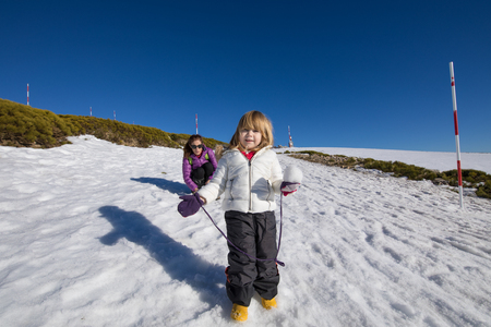 Three years old blonde child with snowball in hand looking, next to woman mother, with white and purple coats on snow in winter mountain