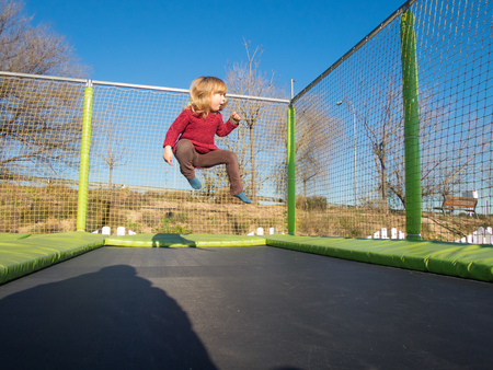 Happy three years old blonde child with winter red sweater trampolining or jumping on trampoline in outdoor playground