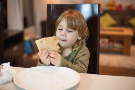 glutton: Three years old blonde hungry child eating pizza piece with her hands, sitting in dark brown chair, in table with grey tablecloth at home
