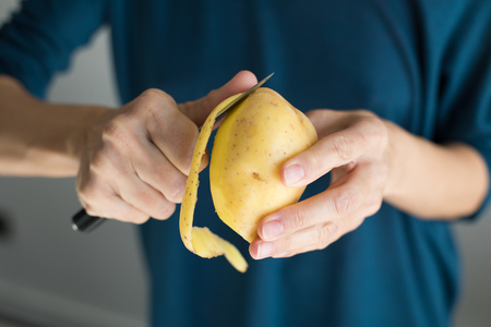 detail of hands of woman with blue sweater peeling fresh yellow potato with kitchen knife, horizontal Stock Photo
