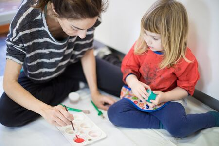 Three years blonde child with red bib and blue trousers next to woman mother sitting on white plastic and paper preparing red watercolor with brush for painting Foto de archivo