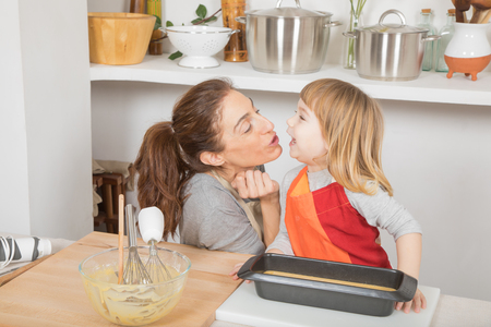 happy tender scene: mother kissing three years old child celebrating finishing sponge cake ready to baking, in teamwork, at kitchen home