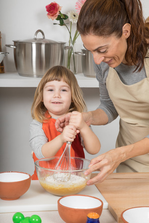 three years old happy child, and woman mother in teamwork, whipping cream in glass bowl with metal whisk to make and cook a sponge cake at kitchen home Stock Photo