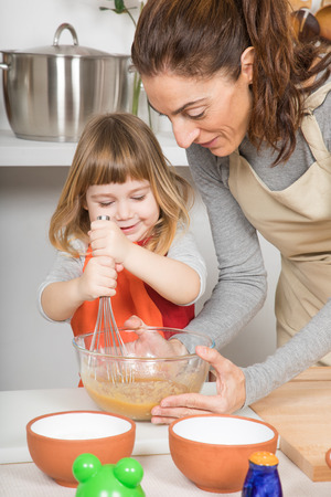 three years old happy child and woman, in teamwork, making and cooking a sponge cake at kitchen home, whipping cream in glass bowl with metal whisk