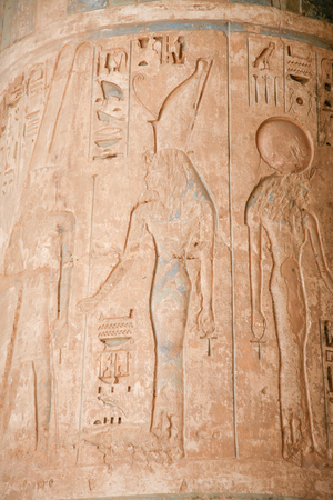 Egyptian carving figure queen and hieroglyphs in column of landmark Temple of Ramses or Ramesses III at Medinet Habu, monument in Luxor, Egypt, Africa