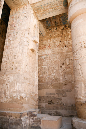 Egyptian paintings, carving figures and hieroglyphs in columns and wall of landmark Temple of Ramses or Ramesses III at Medinet Habu, monument in Luxor, Egypt, Africa Stock Photo
