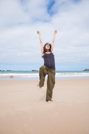 brunette brown hair pregnant woman with grey shirt green trousers and black sunglasses happy joyful dancing in summer on sand beach ocean in Asturias Spain