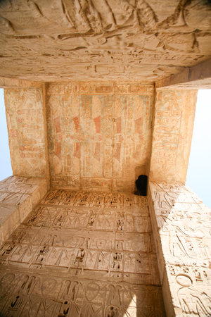 ceiling and wall of landmark Egyptian mortuary Temple of Ramses or Ramesses III at Medinet Habu, monument with carving figures and hieroglyphs, in Luxor, Egypt, Africa