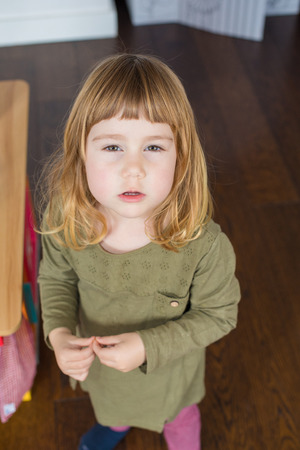Portrait of three years old child face, blonde bang, with green shirt and touching her finger, looking at camera threatening