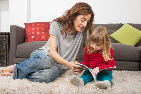 blonde child three years old, with red and green clothes, next to mother woman in jeans, reading together a story tale book, sitting on carpet indoor home Stock Photo