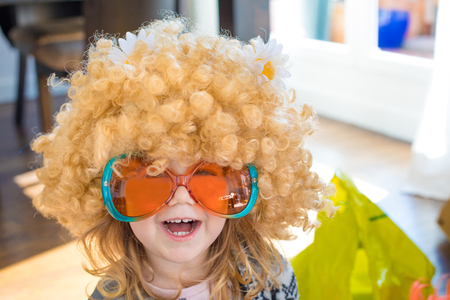 funny portrait of three years old child disguised as sixties, with great curly blond hair wig with daisy flowers on head, with orange and green colorful glasses, looking laughing Stock Photo